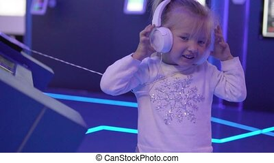 A beautiful little girl is listening to music in collections