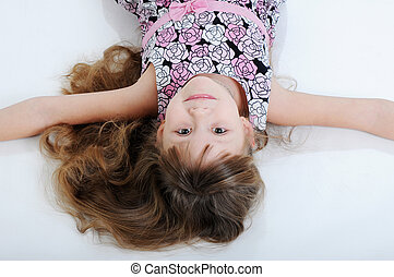 A beautiful little girl lying on the floor