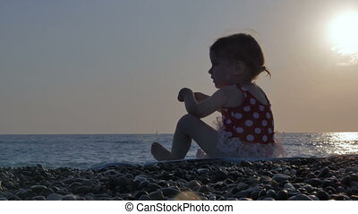 A beautiful little girl of about 2-3 years old sits on the beach and throws stones into the water. Sunset at the sea. The concept of recreation, happy childhood