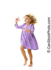 A beautiful little girl stands in the wind, her hair and clothes are developing greatly. The concept of style and fashion.