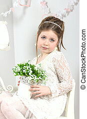 a beautiful little girl with flowers in a pot