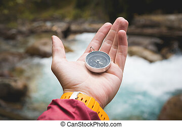 A beautiful male hand with a yellow watch strap holds a magnetic compass in a coniferous autumn forest against a mountain river with rocky stones. The concept of finding yourself the way and the truth.