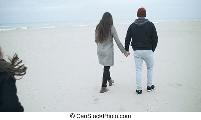 A beautiful married couple is walking along the beach. The...