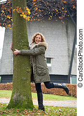 A beautiful middle age woman tree hugging in Europe