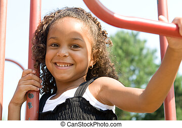 A beautiful mixed race child enjoying the playground