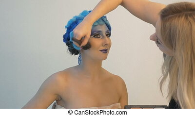A beautiful model participates in a photo session. Makeup artists use special brushes for toned powder.