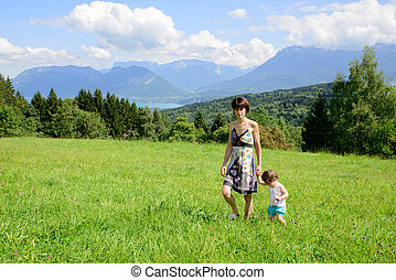 a beautiful mother and daughter walking in the mountains