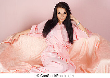 A beautiful nice caucasian girl sitting on the couch in pink