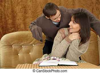 A beautiful nice mother with her son sitting on the couch