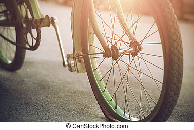 A beautiful old green Bicycle stands on the asphalt