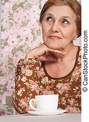 A beautiful older woman sitting at a table