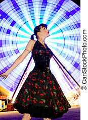 A stock photograph of a beautiful pin up model posing infront of a ferriswheel at night.