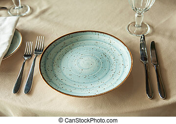 A beautiful plate on the table with forks and knives