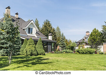 private house with its beautiful garden in a rural area under blue sky