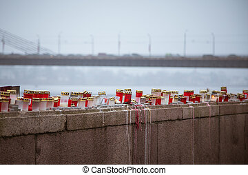A beautiful red and white candles on the railing of a river side in the foggy november morning in Riga