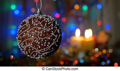 A beautiful red ball. New Year and Christmas decorations. Burning candles. Flashing Garlands. Blurred background.