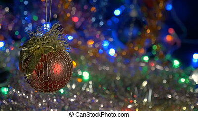 A beautiful red ball. New Year and Christmas decorations. Flashing Garlands. Blurred background.