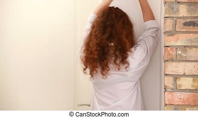 Girl with red curly hair is depressed. Banging his fist on the wall, and crying.