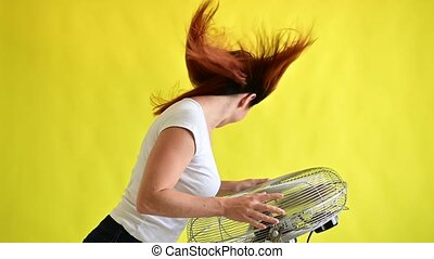 A beautiful red-haired woman is cooled off standing over a large electric fan on a yellow background. Girl with hair developing in the wind. Device for cooling the air