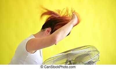 A beautiful red-haired woman is cooled off standing over a large electric fan on a yellow background. Girl with hair developing in the wind over Device for cooling the air. Slow motion