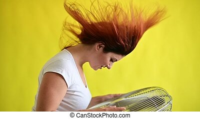A beautiful red-haired woman is cooled off standing over a large electric fan on a yellow background.