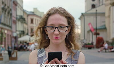 A Beautiful Redhead Using a Mobile Phone Outdoors