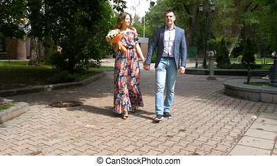A beautiful romantic couple is walking in the park. slow motion