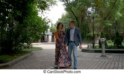 A beautiful romantic couple is walking in the park. Date.