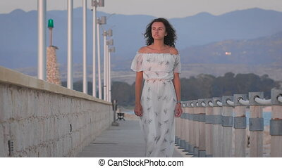 A beautiful romantic sad woman walking at a port