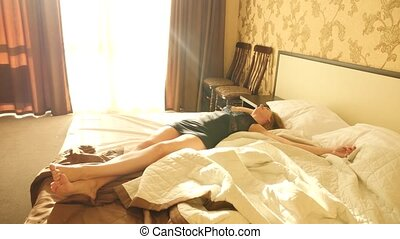 A beautiful romantic woman lying on a bed in her room...