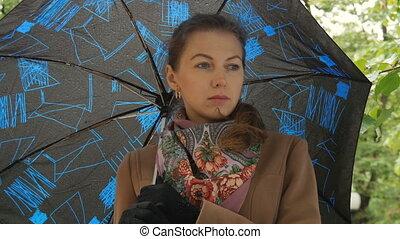 A beautiful sad girl hides from the rain under an umbrella close-up