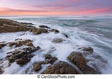 A beautiful seascape with rocks and crashing waves in the foreground