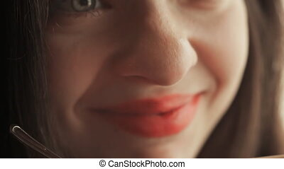 A beautiful sensual girl enjoys tea. Face close-up.