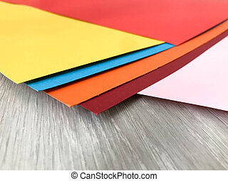 A beautiful set of red yellow orange blue burgundy colored cardboard paper sheets. The background