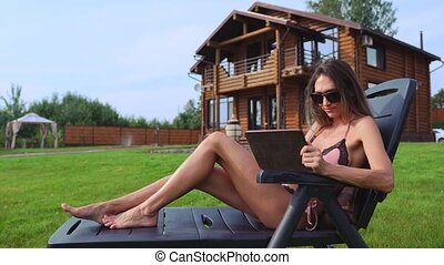 A beautiful sexy woman lying on a sun lounger in the backyard of her mansion is doing online shopping with a tablet computer