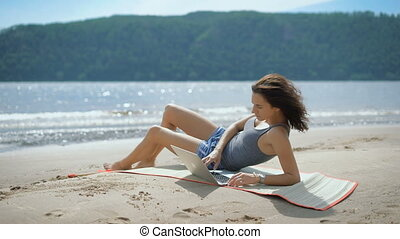 A beautiful sexy young lady is laying at a beach using laptop