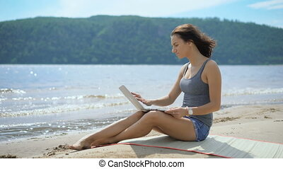 A beautiful sexy young lady is sitting at a beach using laptop