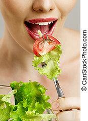 eating healthy food - A beautiful slender girl eating ...