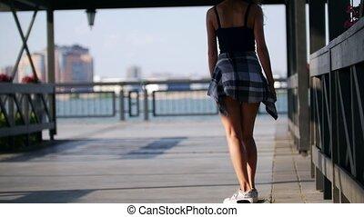 A beautiful slender girl rides a skateboard along the...