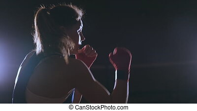 A beautiful sports boxer woman in red bandages on her hands and a blue t-shirt is fighting with a shadow practicing the speed and technique of punches. Camera movement side View. Steadicam shot. Preparing for self-defense.