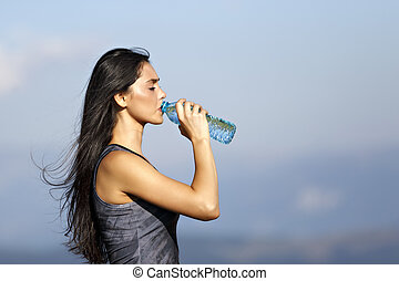 A beautiful sporty caucasian girl drinking water after exercise