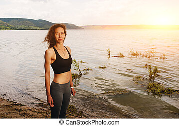 A beautiful sporty woman standing on the shore of a lake in sportswear and preparing for an exercising