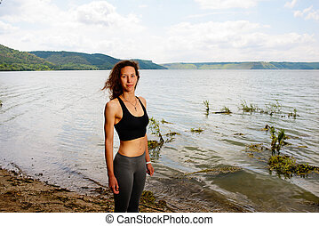 A beautiful sporty woman standing on the shore of a lake in spor