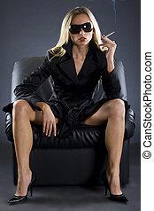 A beautiful spy lady sitting on a sofa, smoking a cigarrette