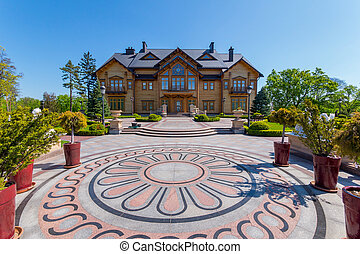 A beautiful square in front of the house with floral patterns and flowers-trees in the horsemen around