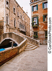 A beautiful stone bridge with a staircase across the Venetian Canal on the streets of Venice, in Italy. The facades of beautiful brick buildings with Venetian-style windows and wooden shutters.