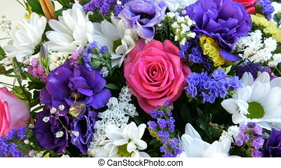 A beautiful stylish bouquet of various multi-colored flowers of daisies, roses, dried flowers. Festive bridal bouquet of white, pink, blue, purple, yellow flowers.