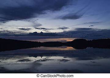 A beautiful sunset over a forest lake with clouds reflected in the water