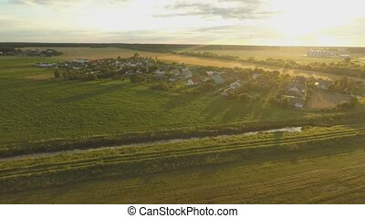 A beautiful sunset over the Russian village. Fields and trees around. Aerial and video shooting.