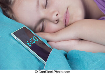A beautiful tranquil girl sleeps on the bed, next to her phone, soon the alarm will ring.